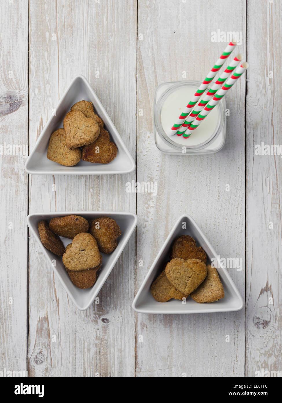 Des cookies en forme de cœur et de lait sur la table en bois blanc Photo Stock