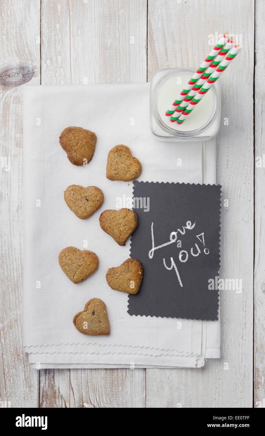 Les cookies en forme de cœur, lait et 'aime' carte manuscrite Photo Stock