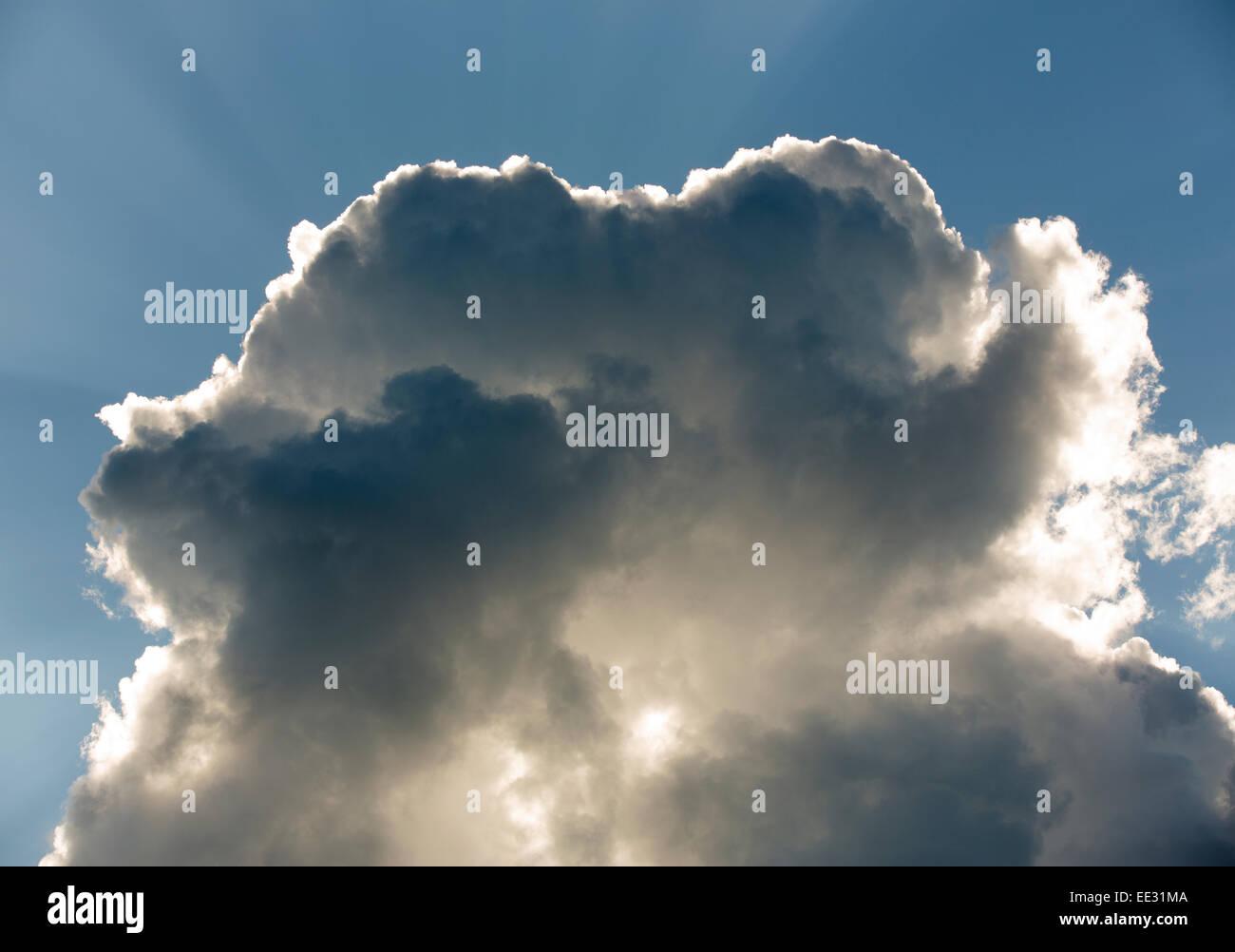 Les rayons du soleil derrière les nuages sombres Photo Stock