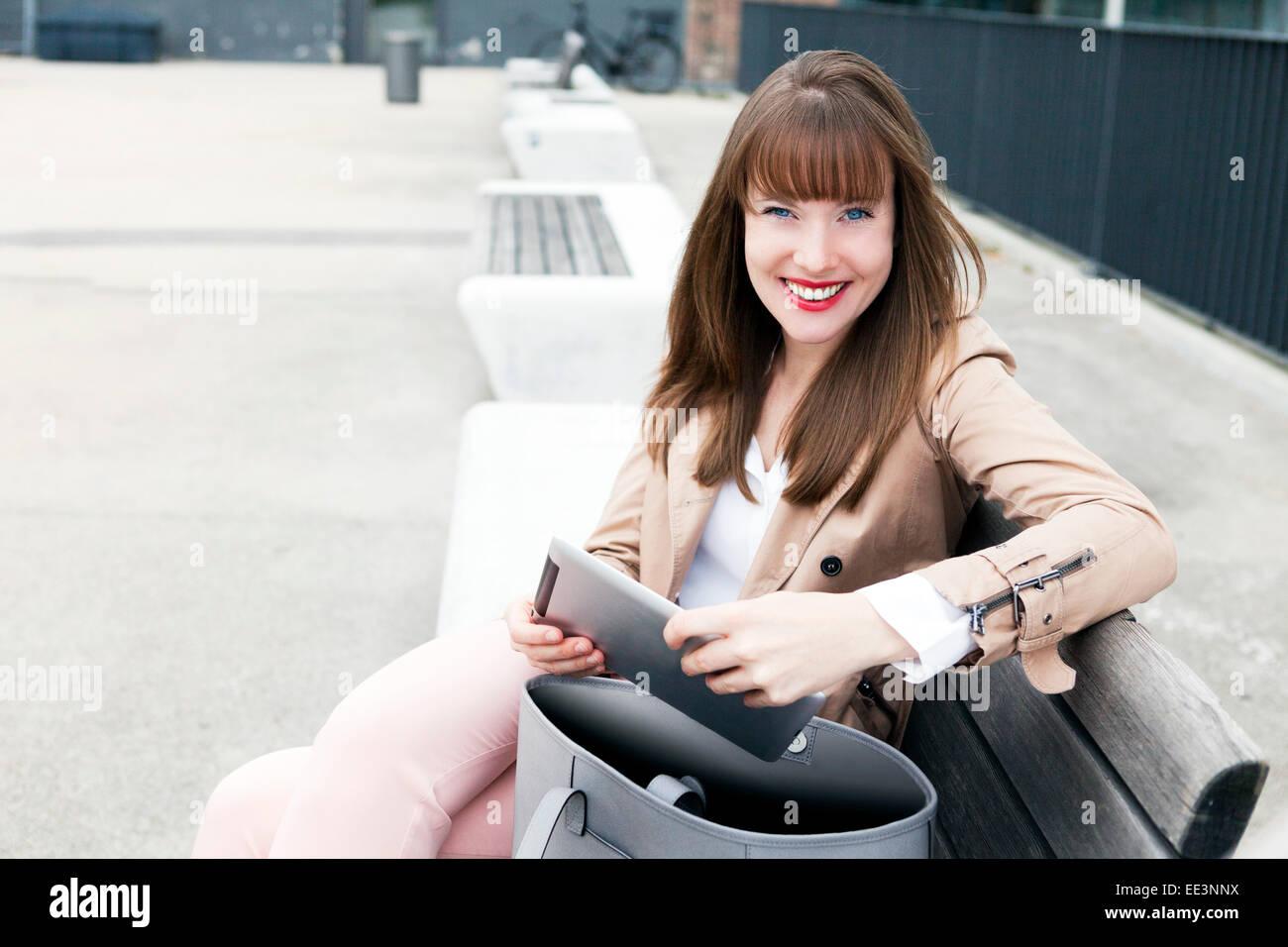 Jeune femme assise sur un banc à l'extérieur, Munich, Bavière, Allemagne Photo Stock