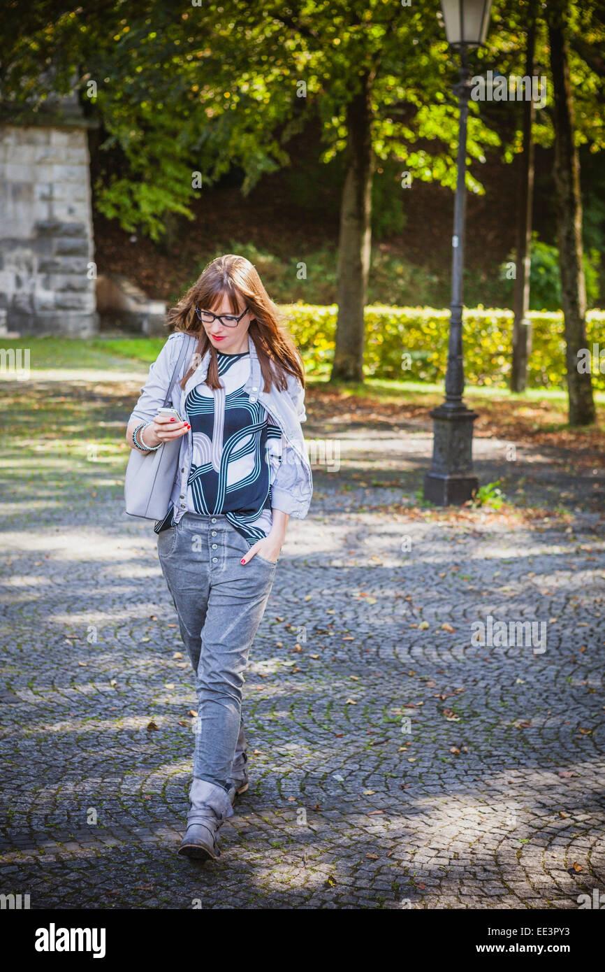 Jeune femme à l'extérieur de la messagerie texte, Munich, Bavière, Allemagne Photo Stock