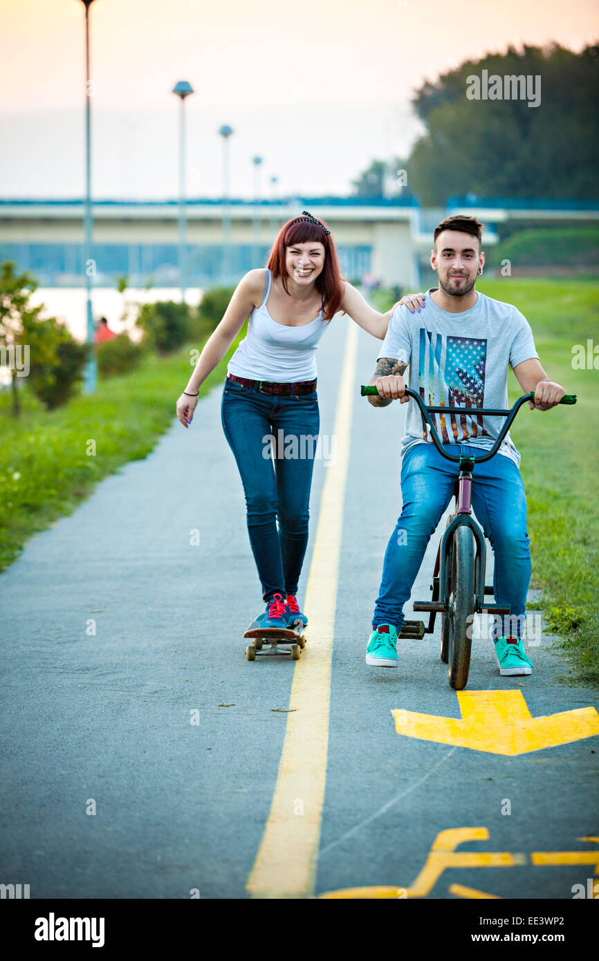 Jeune couple avec vélo BMX et skateboard en plein air Banque D'Images