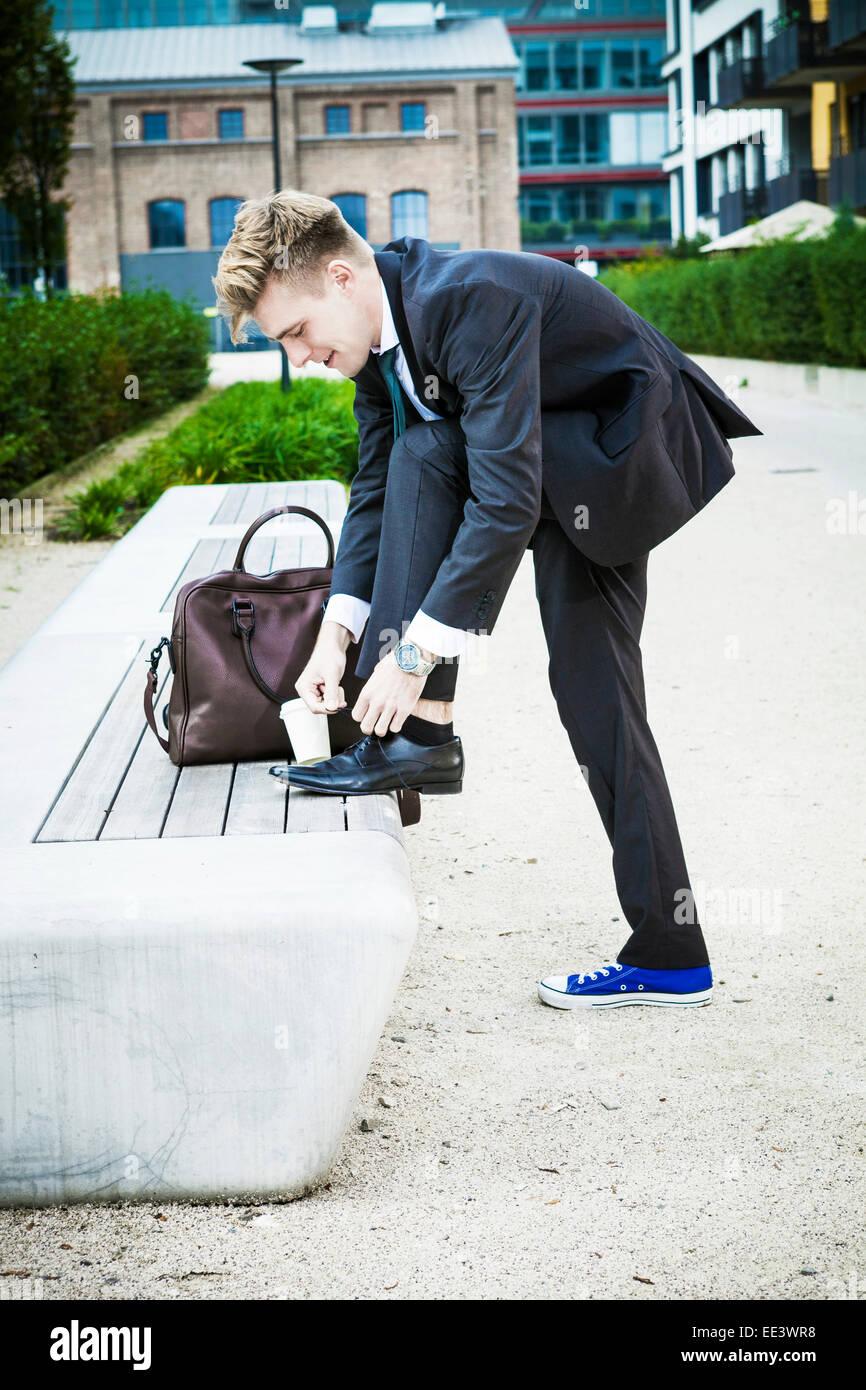 Young businessman putting sur les chaussures, Munich, Bavière, Allemagne Photo Stock