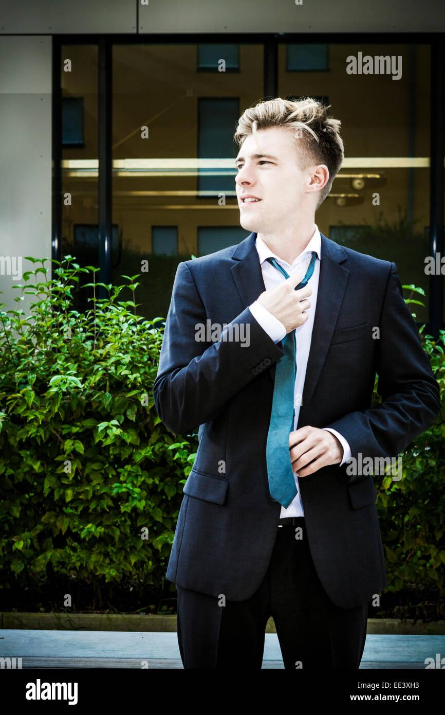 Jeune homme d'ajuster sa cravate, Munich, Bavière, Allemagne Photo Stock