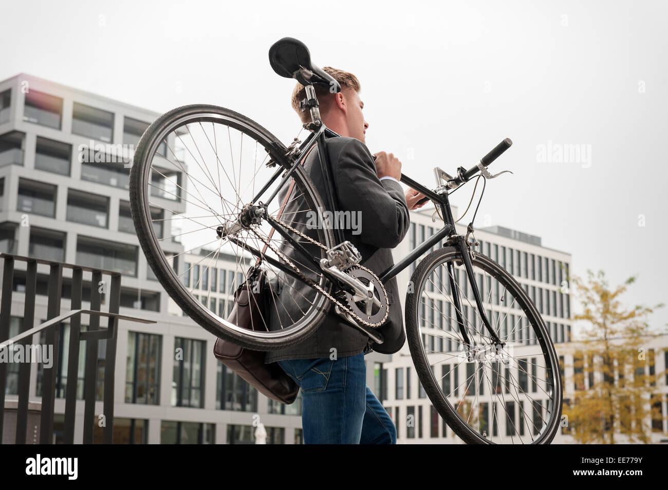 Young businessman carrying bicycle, Munich, Bavière, Allemagne Photo Stock