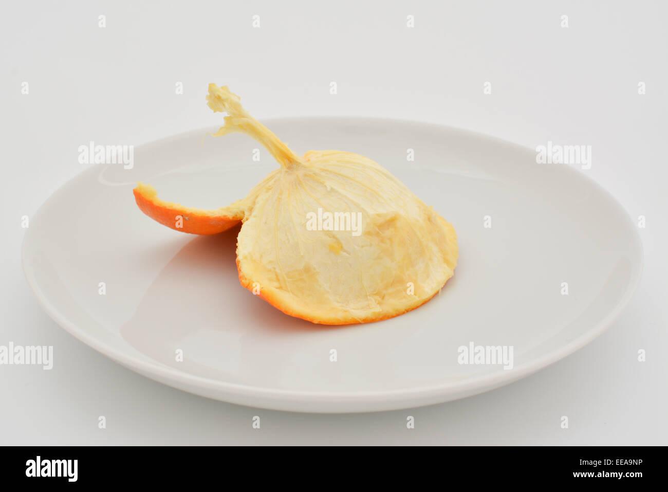 L'intérieur de la peau d'une orange mangée sur une plaque blanche Photo Stock