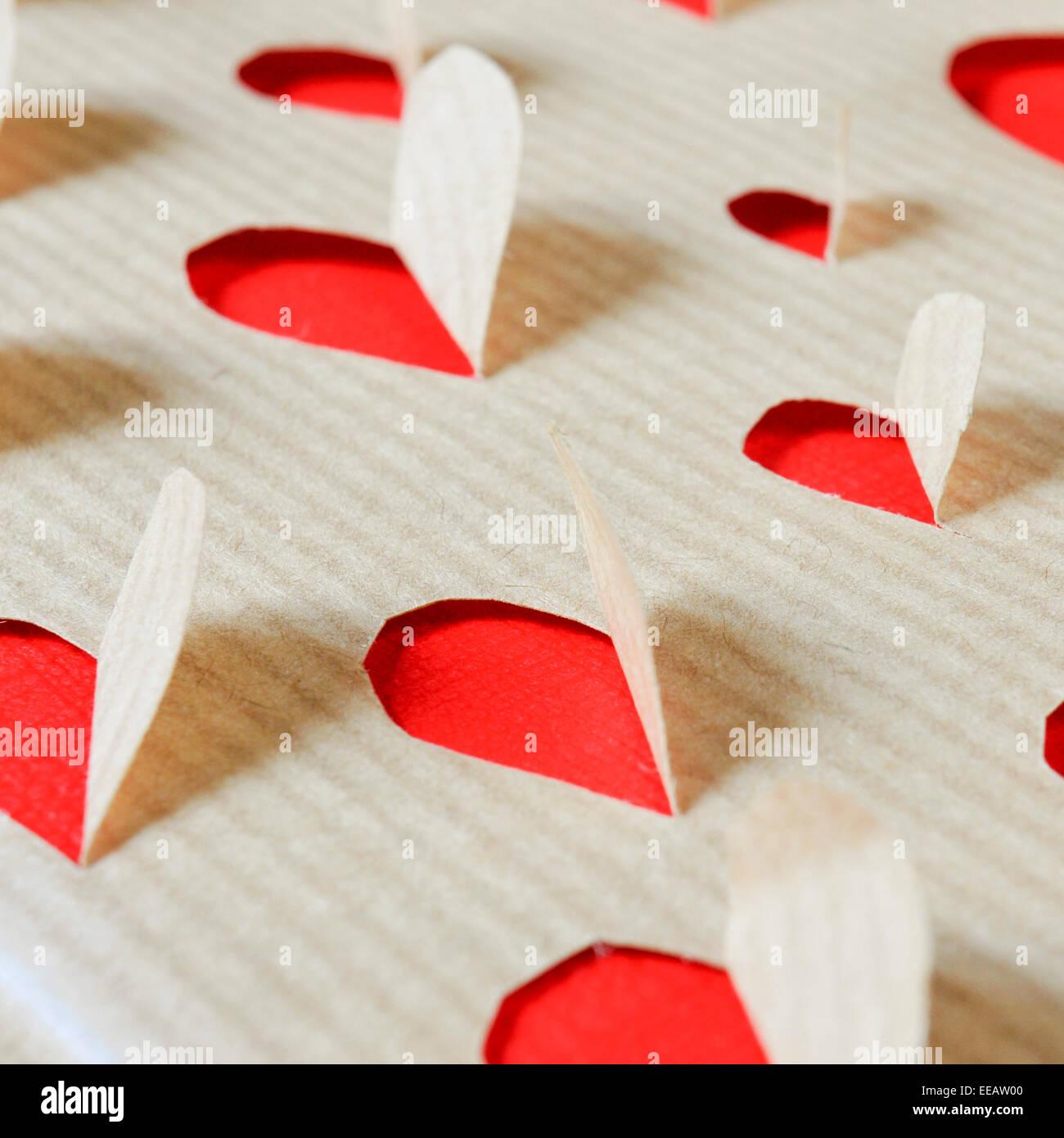 Trous sur un papier kraft formant cœurs Photo Stock