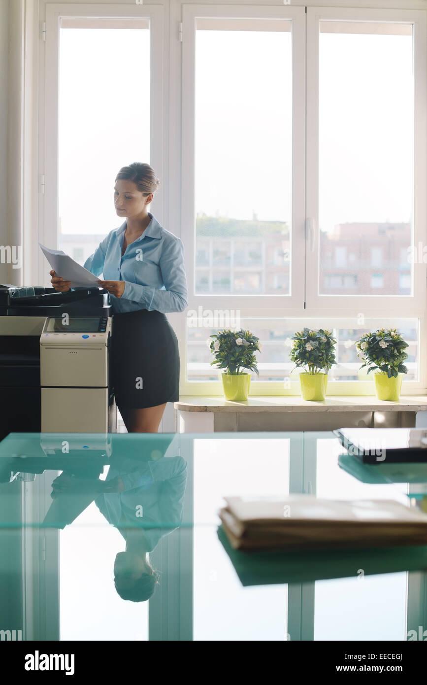 Femme secrétaire travaillant dans le document du bureau, la copie et la paperasse avec copie à la machine Photo Stock
