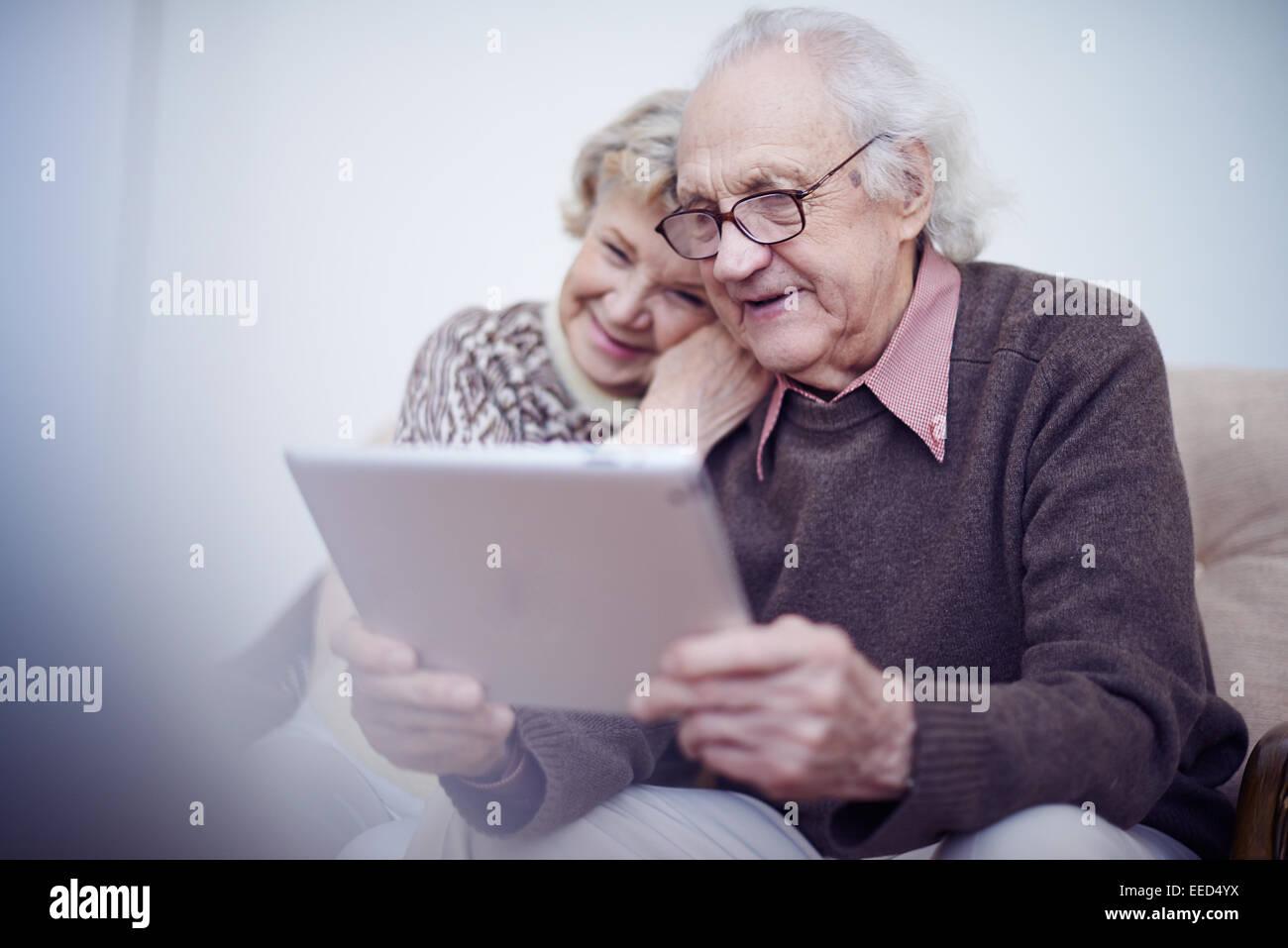 Personnes âgées mari et femme en utilisant le pavé tactile Photo Stock