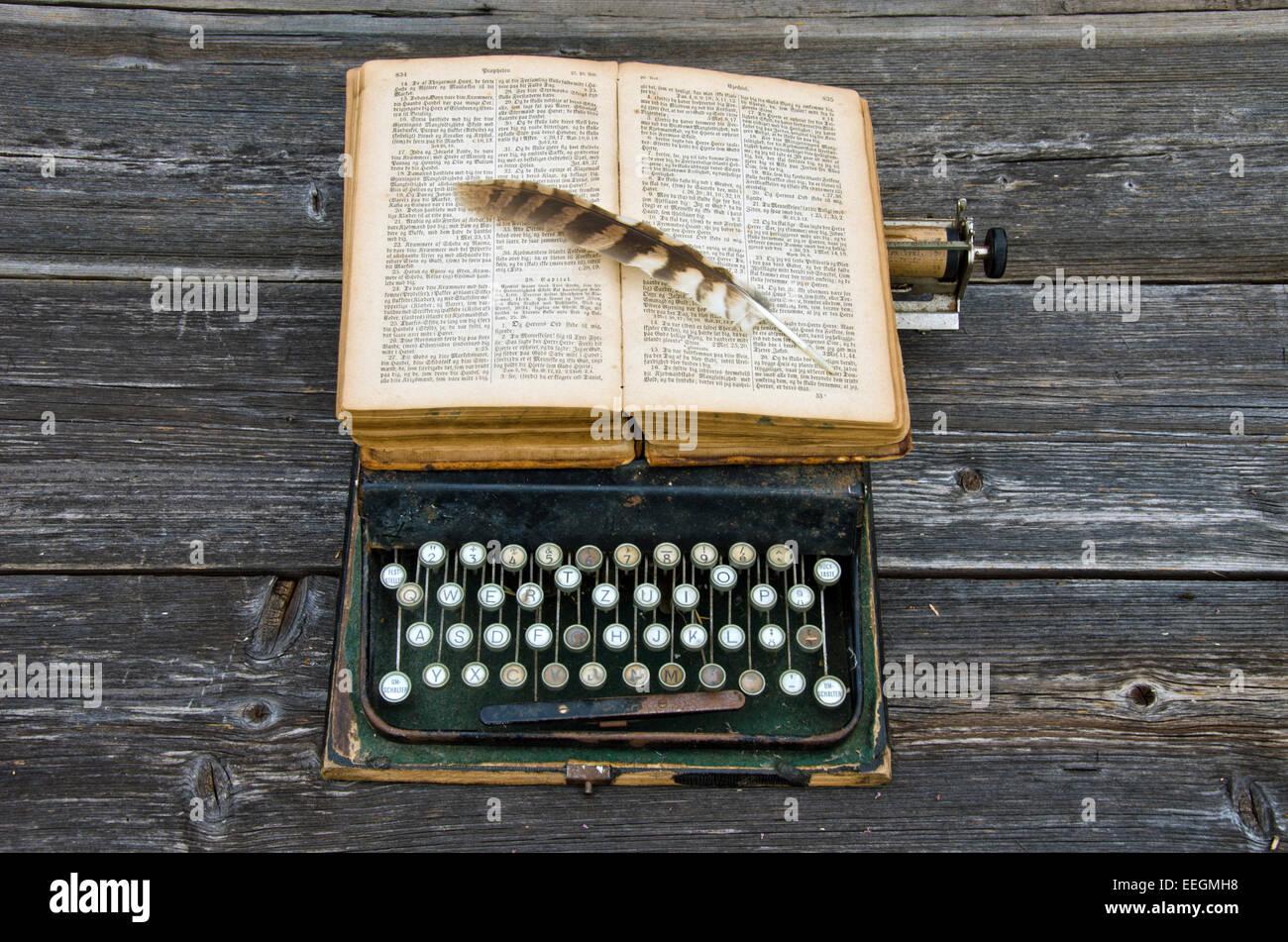 Machine à écrire antique avec vieux livre Bible et plume d'oiseau sur clavier utilisé Photo Stock