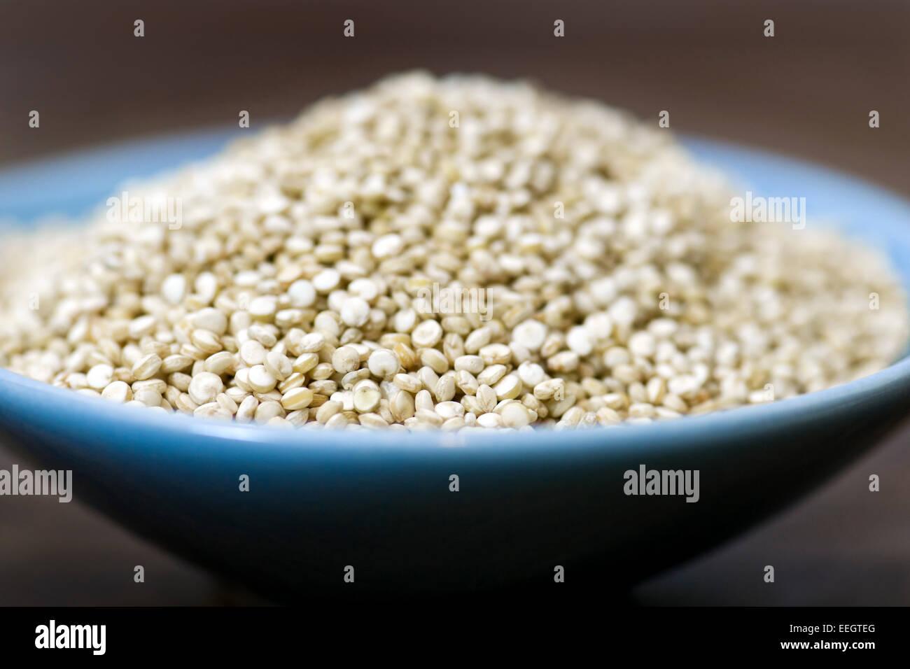 Petit bol bleu rempli de quinoa séchées Photo Stock