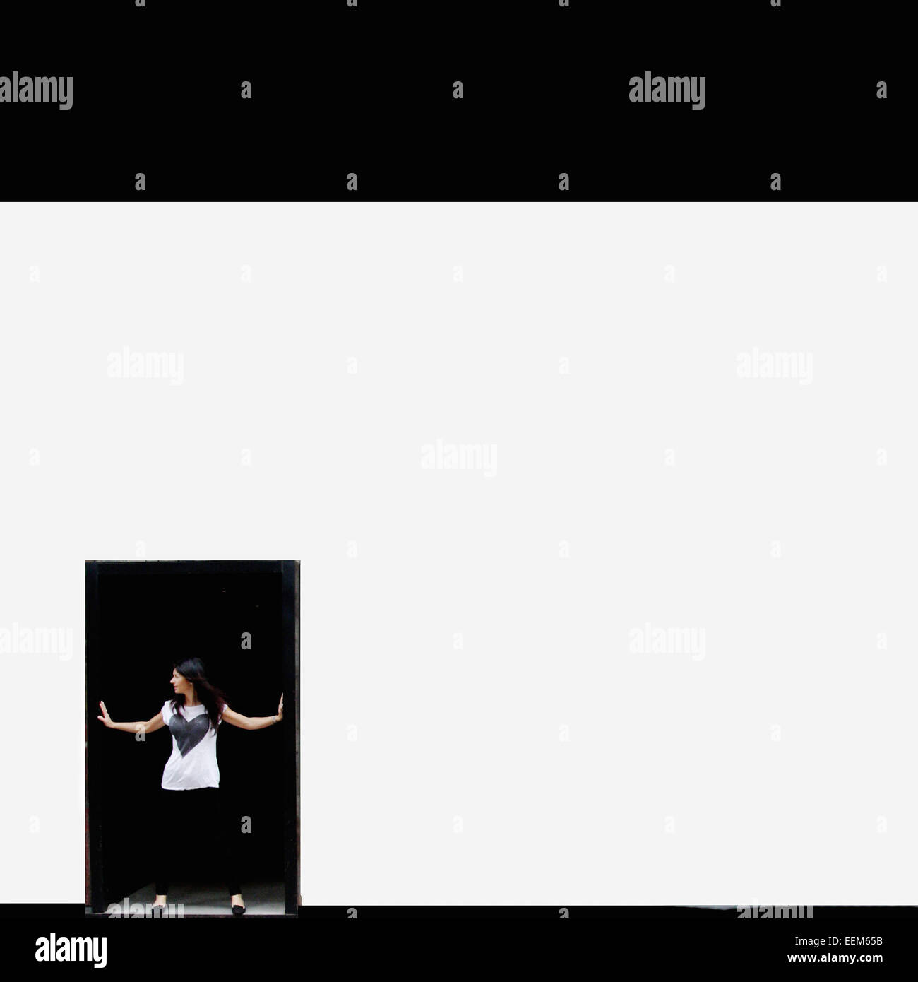 Woman standing in doorway with arms outstretched Photo Stock
