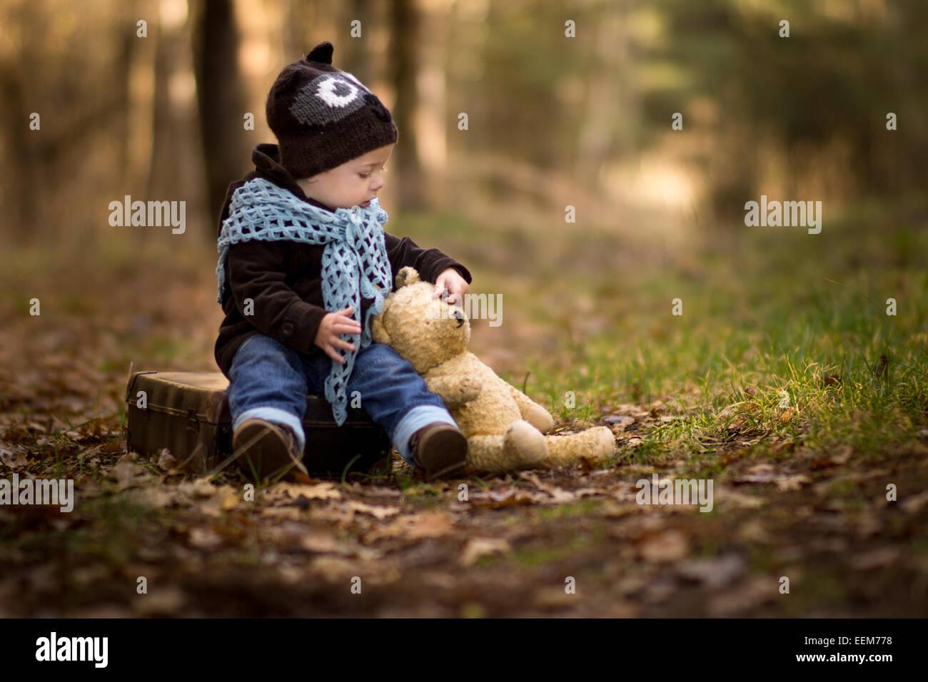 Portrait of baby boy sitting en forêt avec son ours en peluche Photo Stock