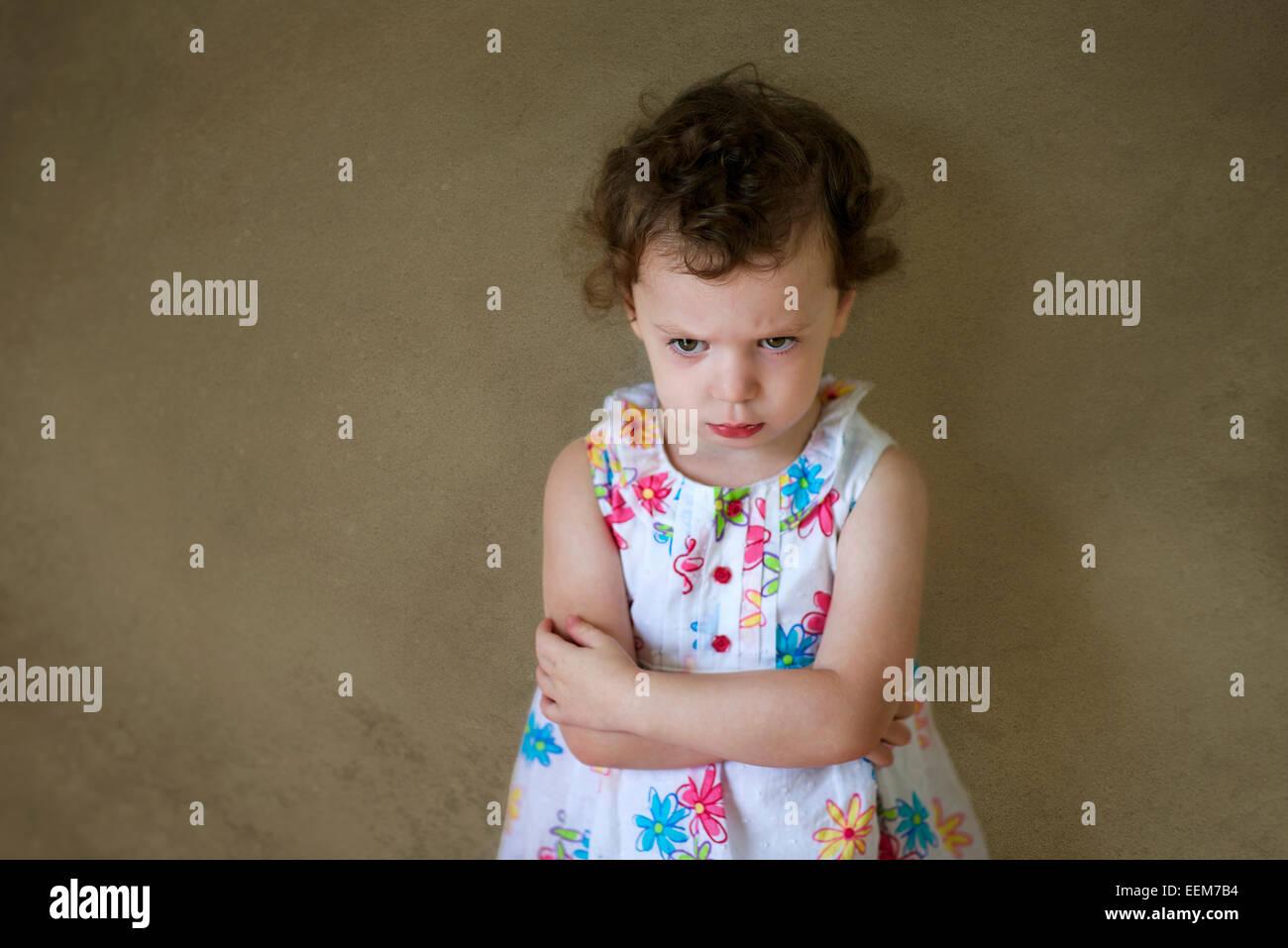 Grumpy girl (2-3) en robe à motifs floraux en mur avec les bras croisés Photo Stock