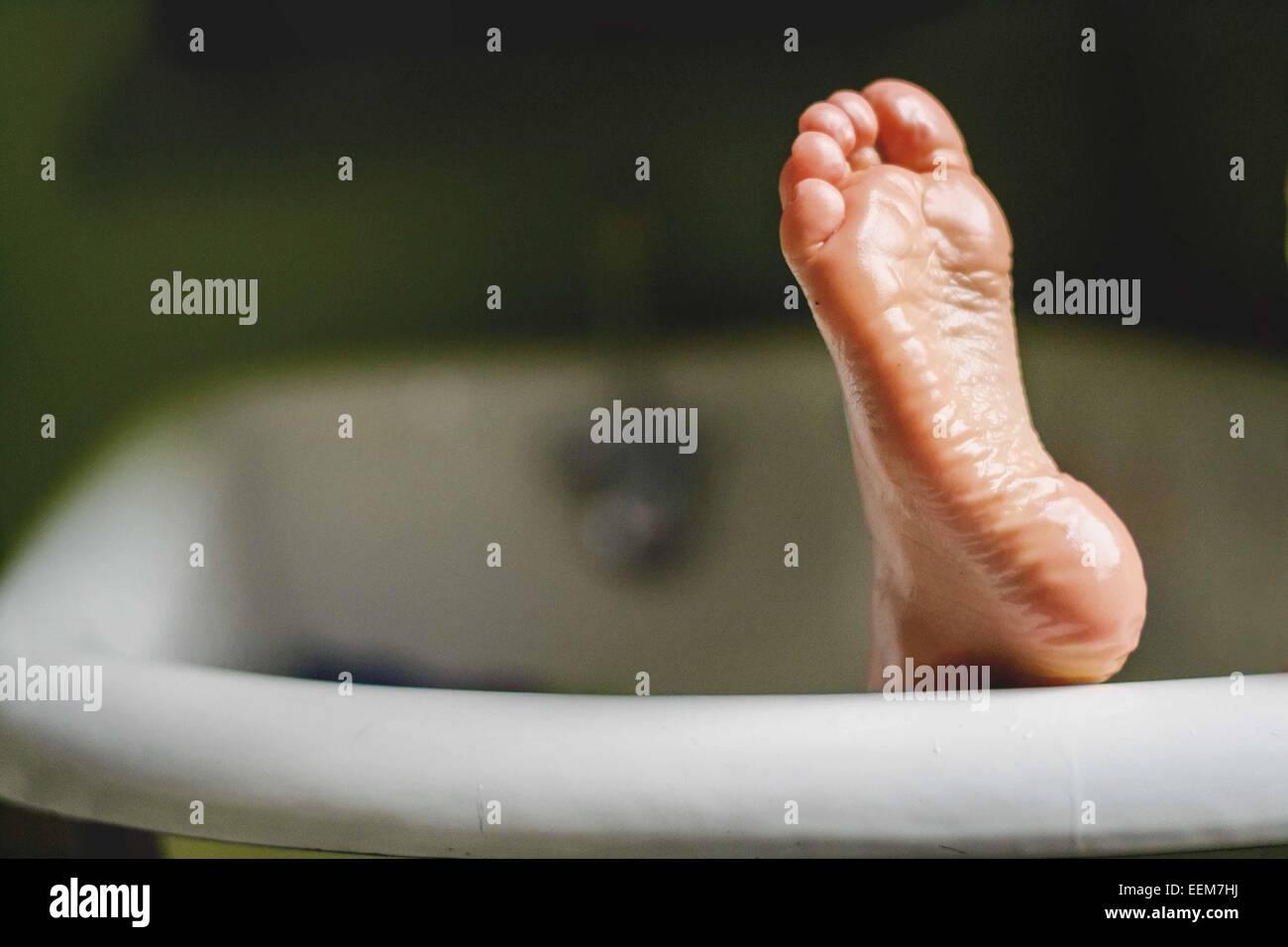L'enfant (4-5) foot sortant de baignoire Photo Stock