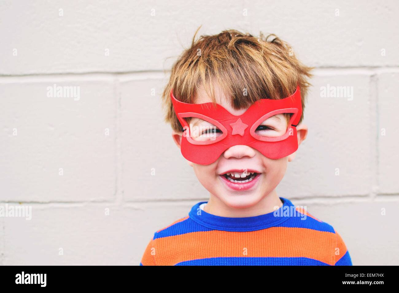 Young boy (2-3) wearing smiling masque de super héros Photo Stock