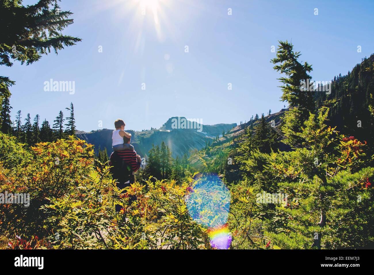 Jeune garçon (2-3) assis sur les épaules du père à la montagne à Photo Stock