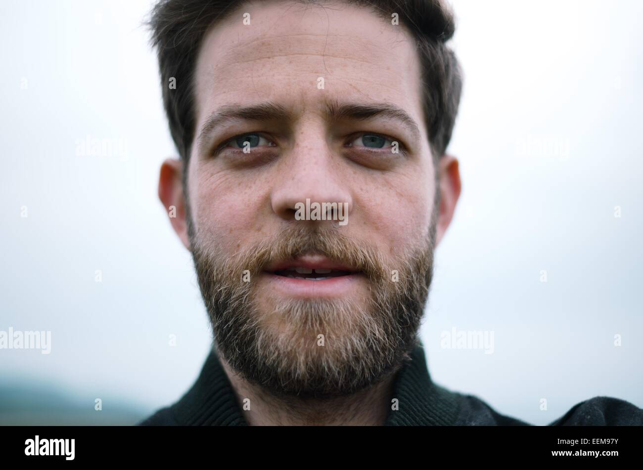 Homme avec barbe looking at camera Photo Stock