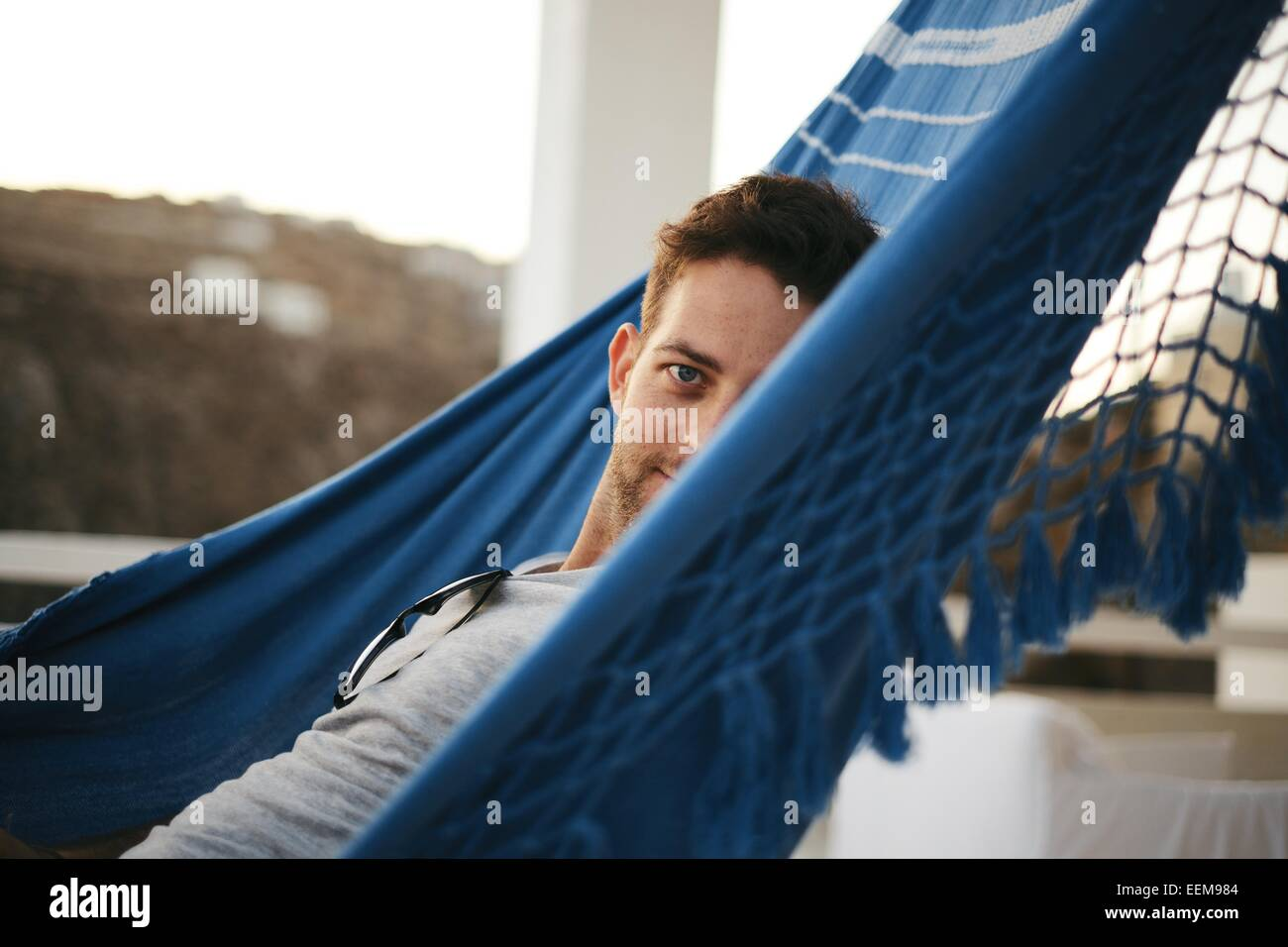 Man laying in hammock and looking at camera Photo Stock