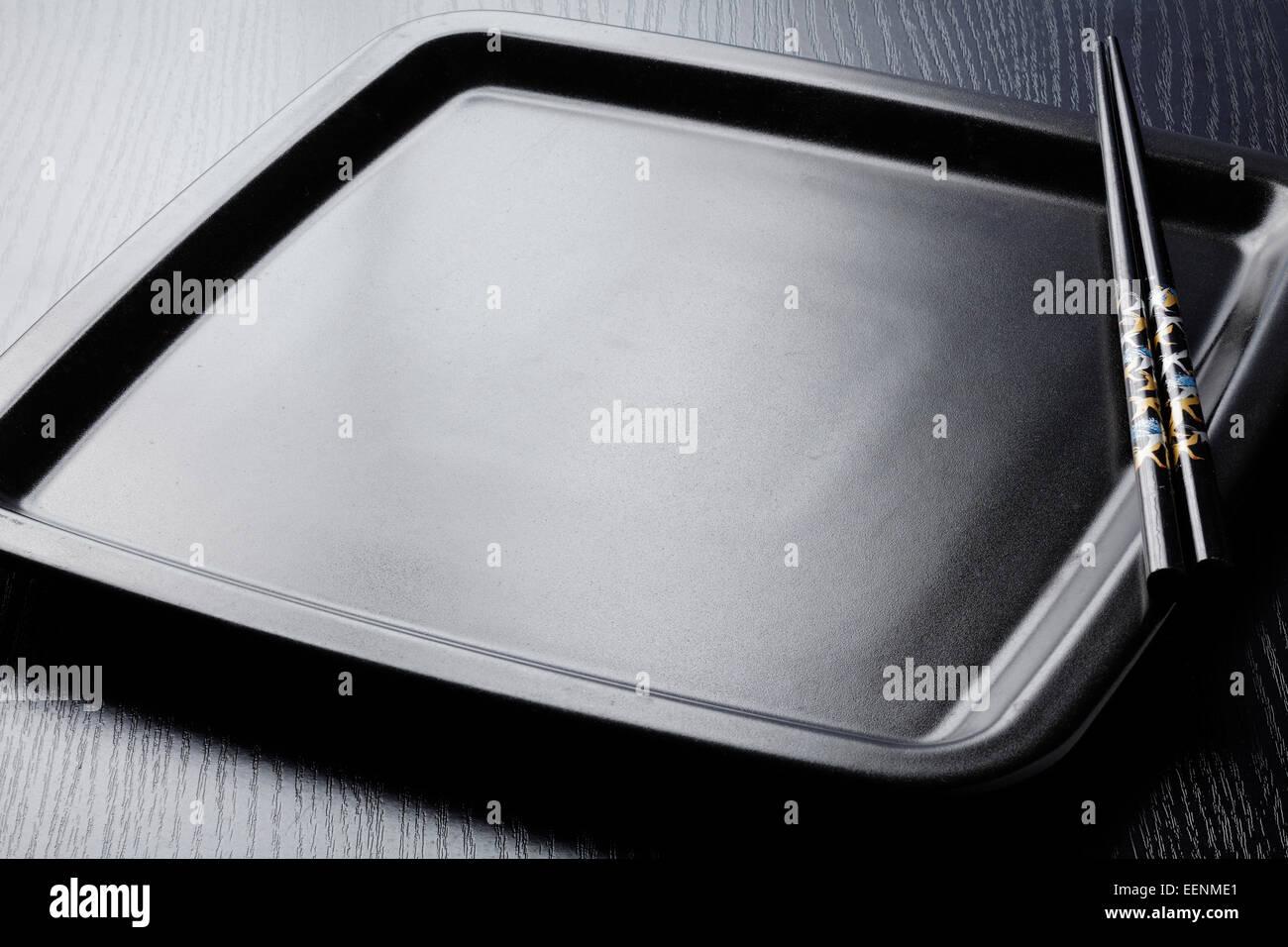 Plaque noir sur noir avec des baguettes en bois noir Photo Stock