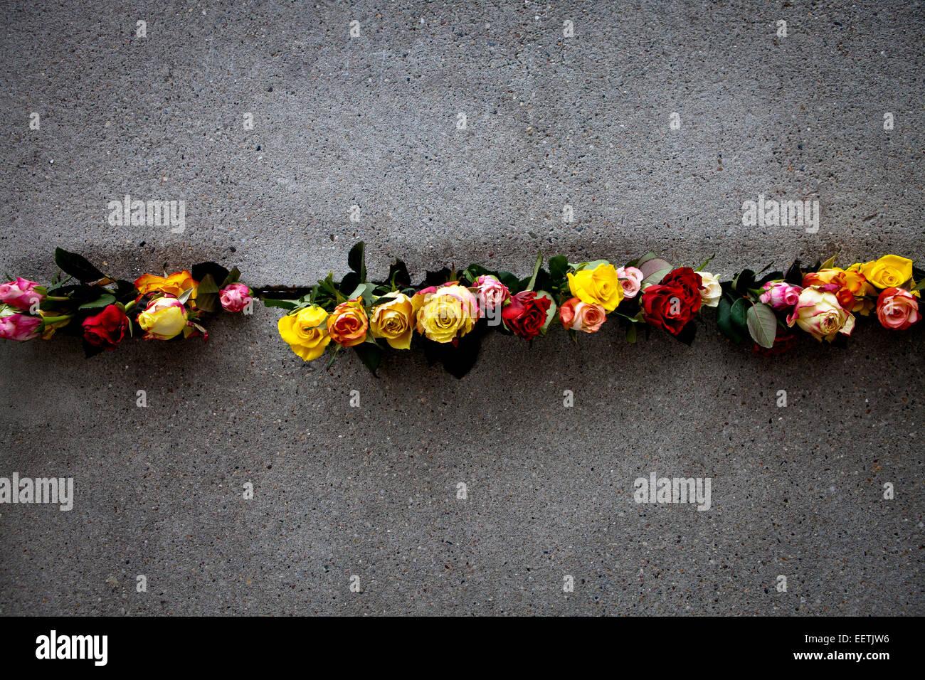 Fleurs placées dans le mur de Berlin au cours de 25e commémoration de sa chute Photo Stock