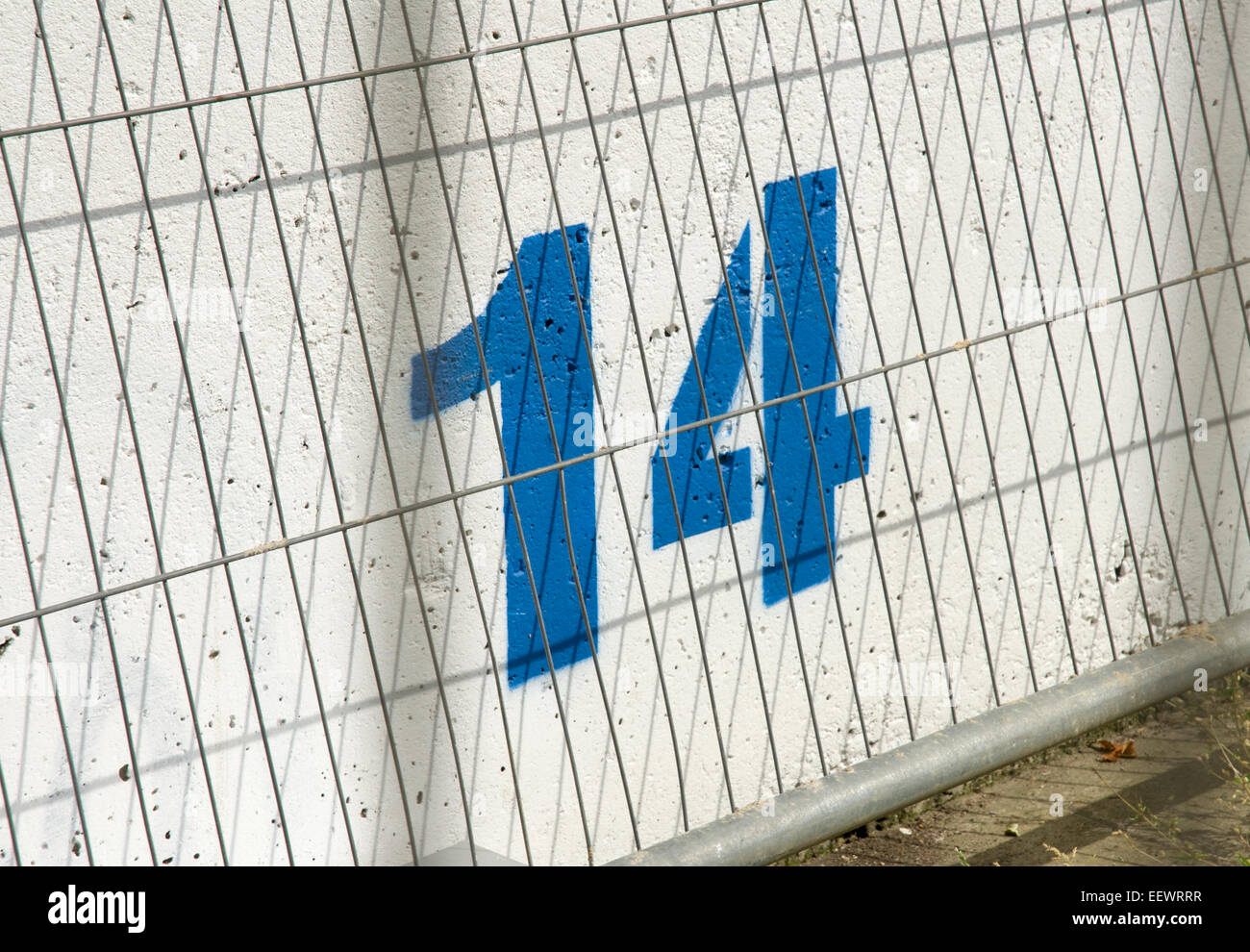 Numéro 14 14 peintes en bleu sur un mur de béton tout en Photo Stock