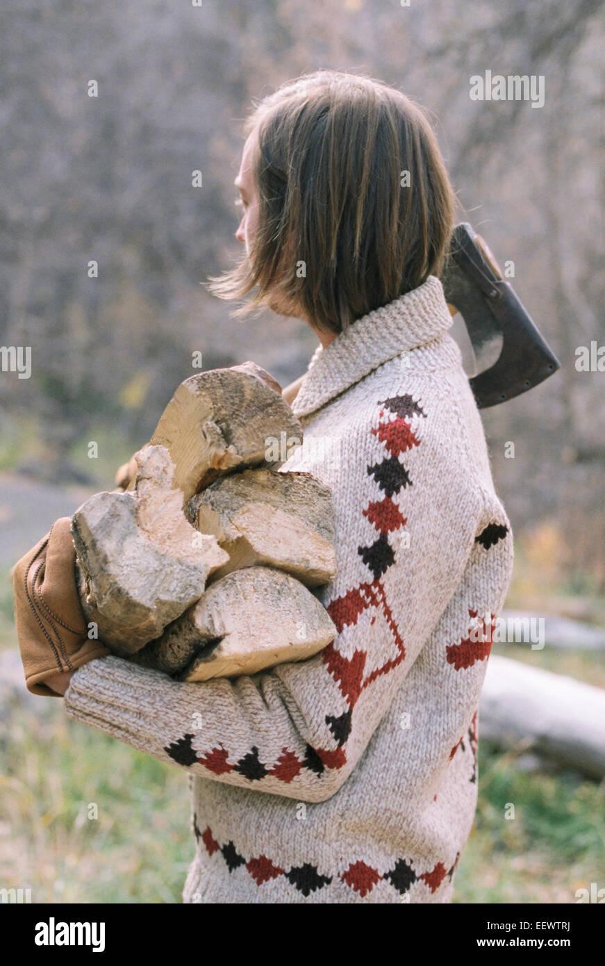 Jeune homme blond transportant du bois de chauffage. Photo Stock