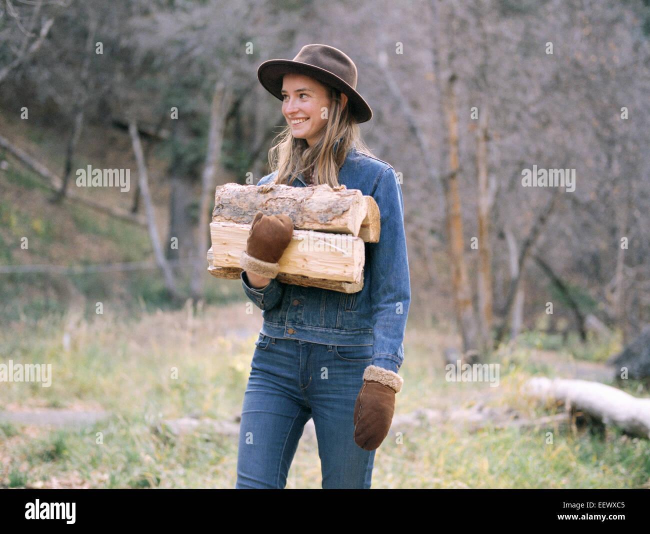 Jeune femme blonde portant un chapeau transportant du bois de chauffage. Photo Stock