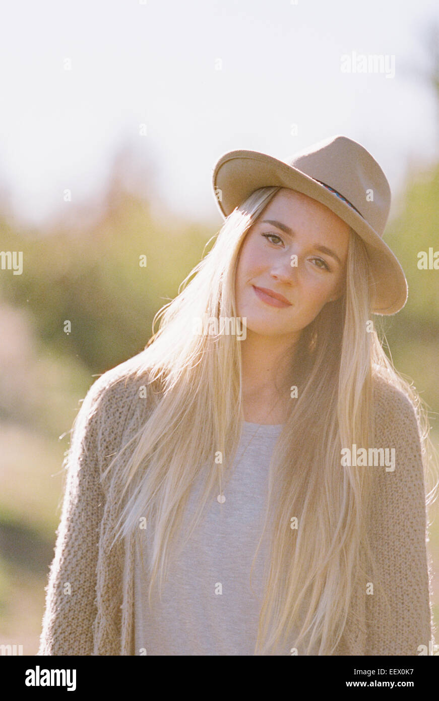 Femme avec de longs cheveux blonds, portant un chapeau. Photo Stock