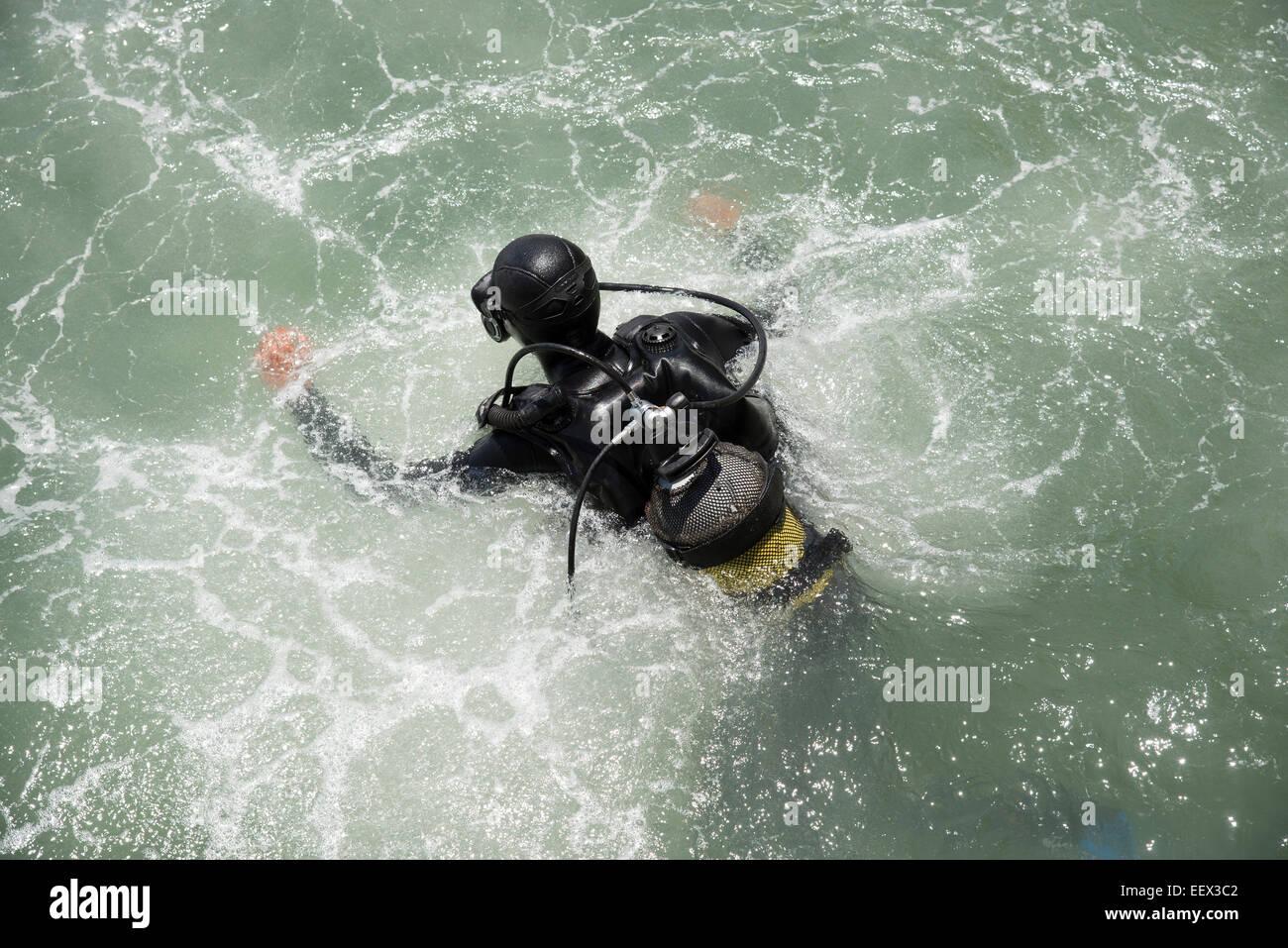 Plongeur commercial entrant dans l'eau avec une éclaboussure Photo Stock