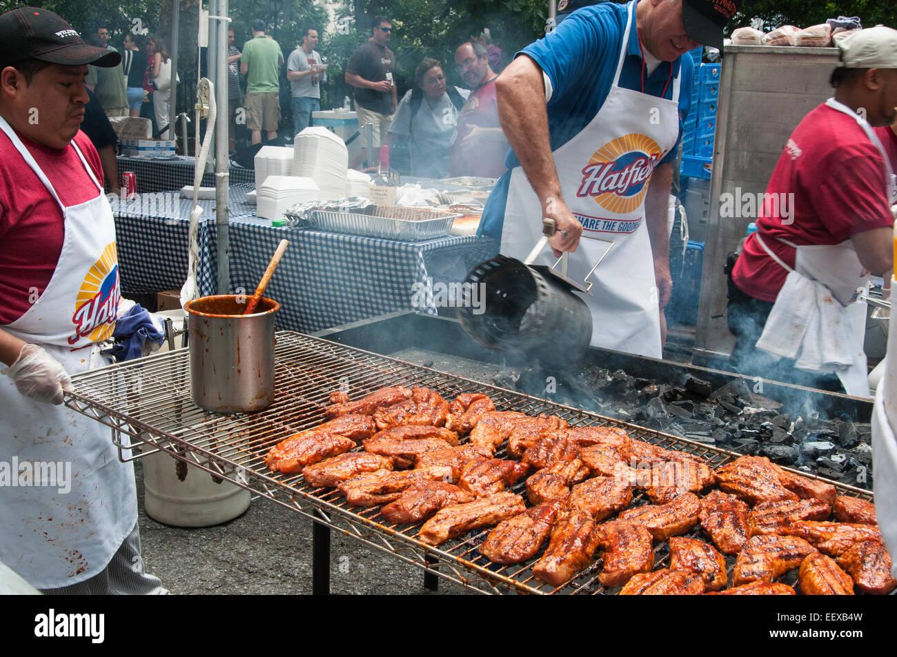 Une fosse patron en remuant de charbon de bois à New York city's Big Apple BBQ. Photo Stock