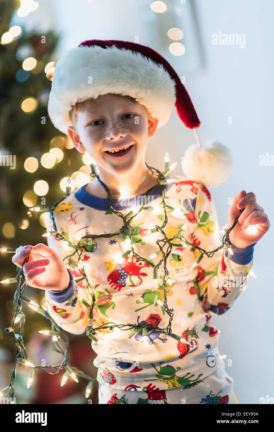Portrait of boy (6-7) holding christmas lights Banque D'Images
