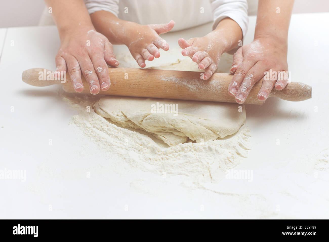 Mère et fille mains pétrissant la pâte sur la table. Photo Stock