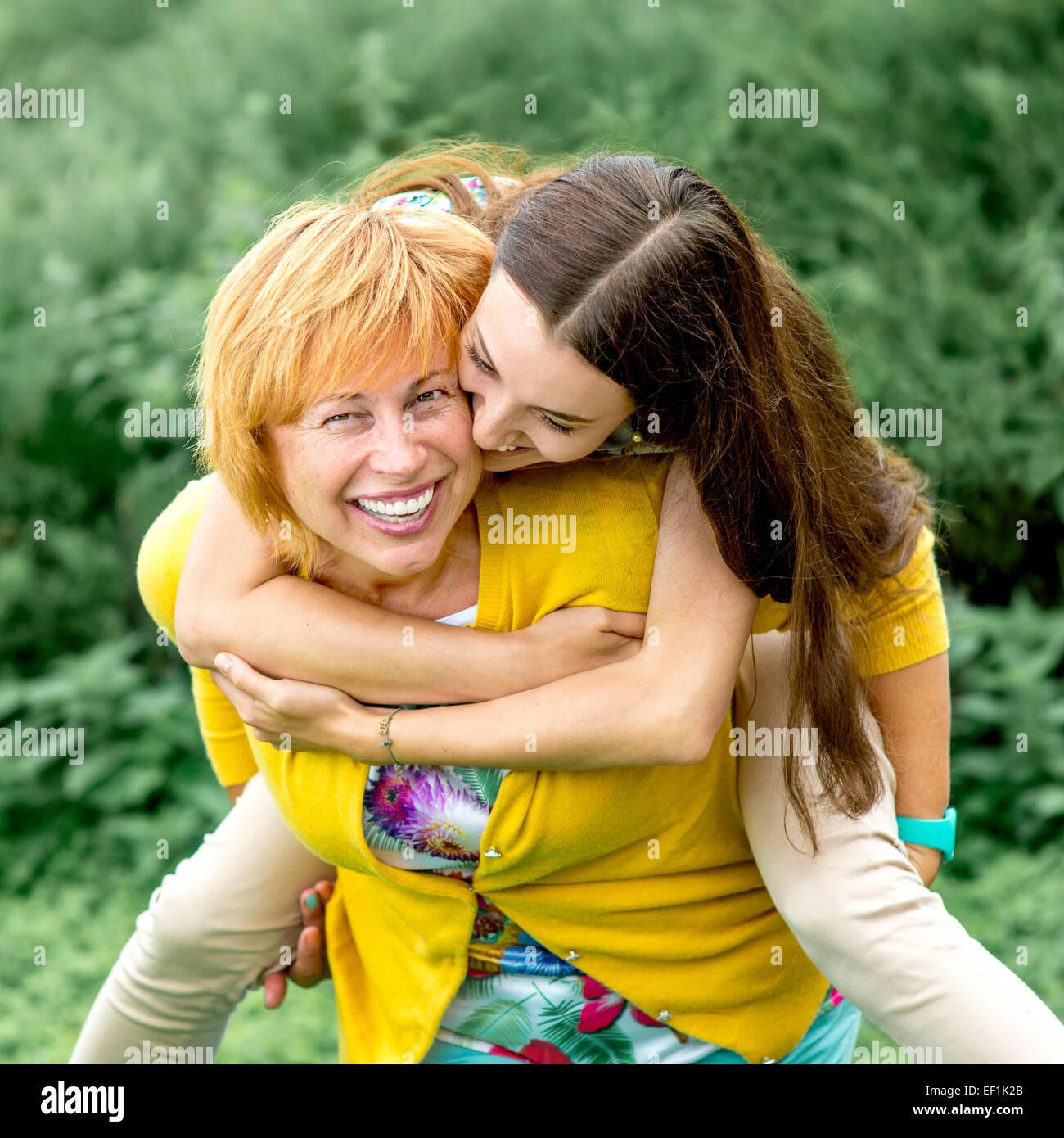 Mother riding piggyback à sa fille dans le parc Photo Stock