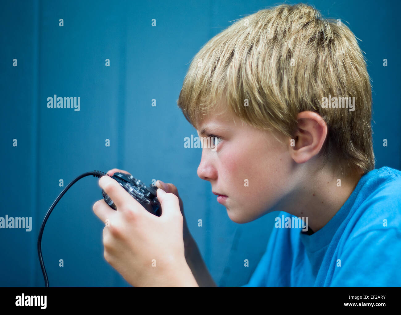 Jeune garçon, 10-11-12-13, jeux vidéos à l'aide de concentration avec contrôleur Photo Stock