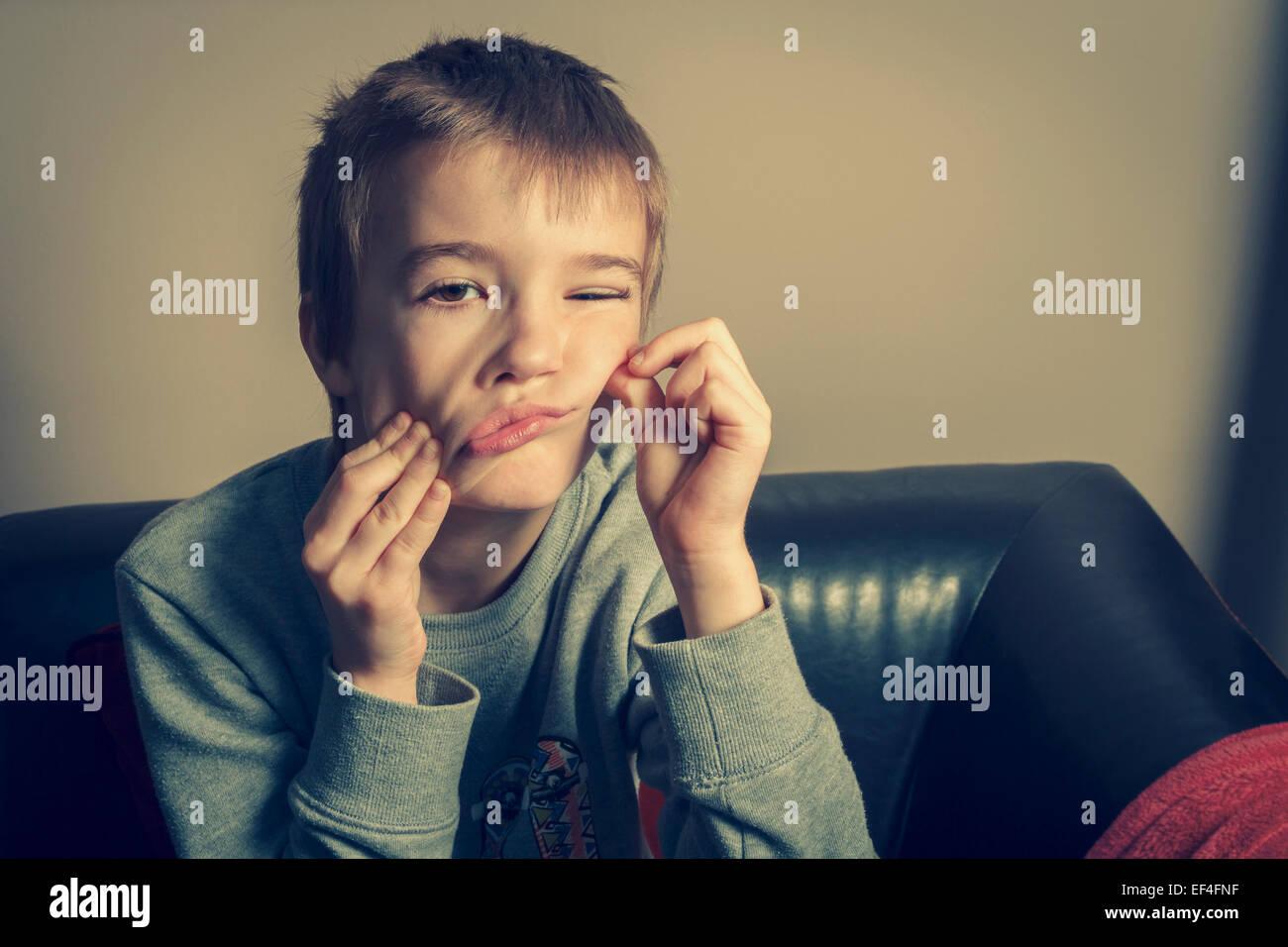 Jeune garçon dans la salle de séjour faire un visage. Photo Stock