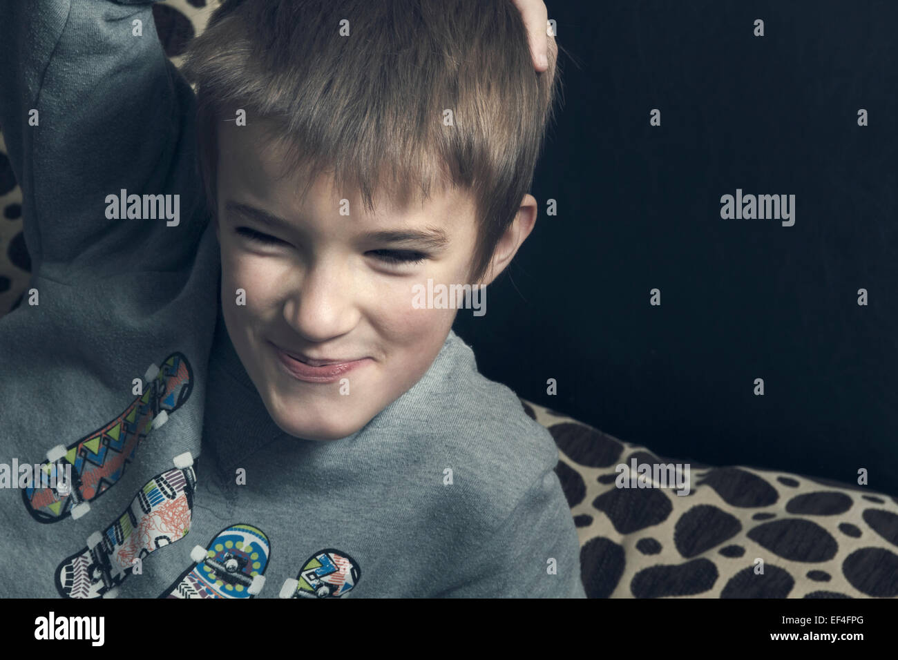 Jeune garçon dans le salon en riant. Photo Stock