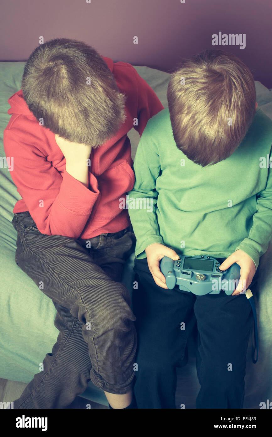 Deux jeunes garçons dans la chambre de jouer à un jeu vidéo. Photo Stock