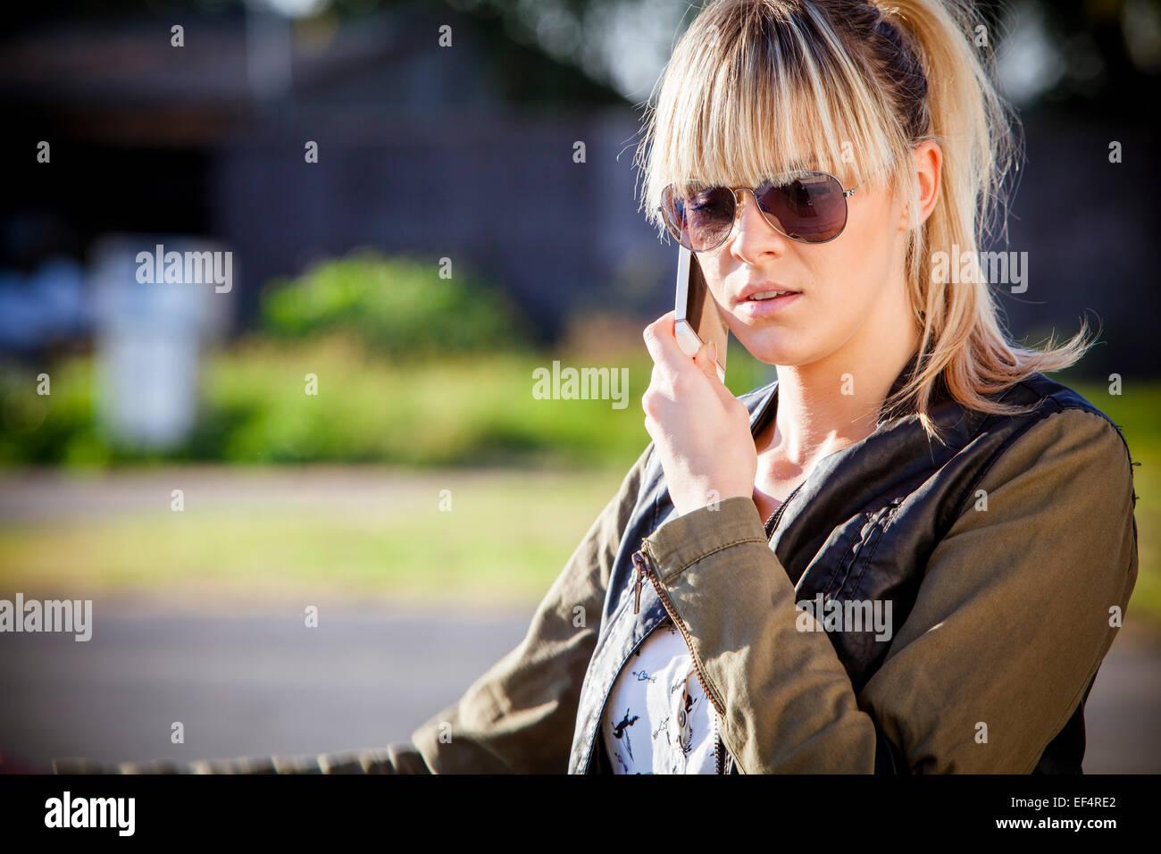 Jeune femme avec des lunettes à l'aide de mobile phone Photo Stock