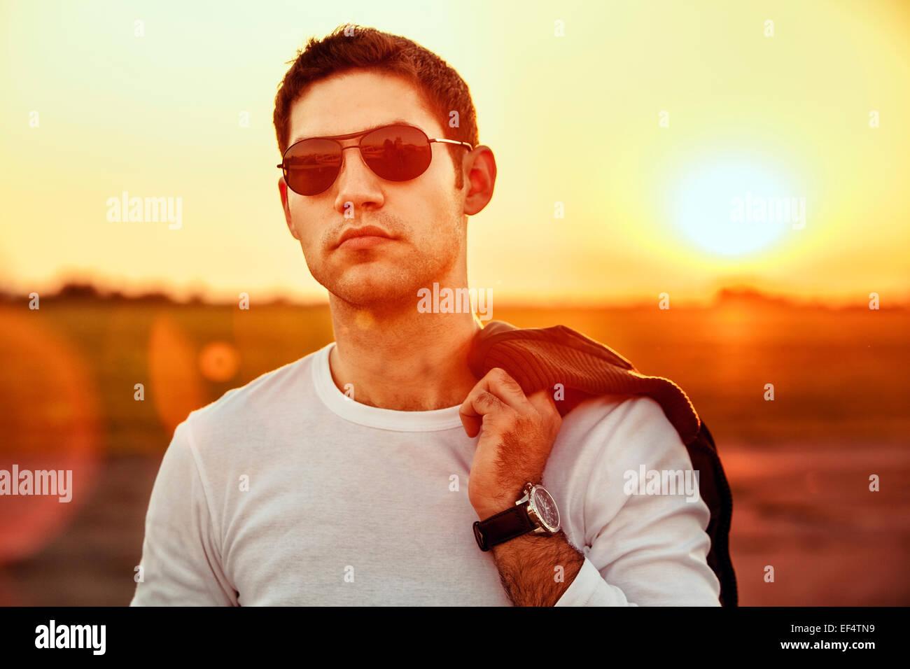 Portrait de jeune homme avec des lunettes de soleil au coucher du soleil Photo Stock
