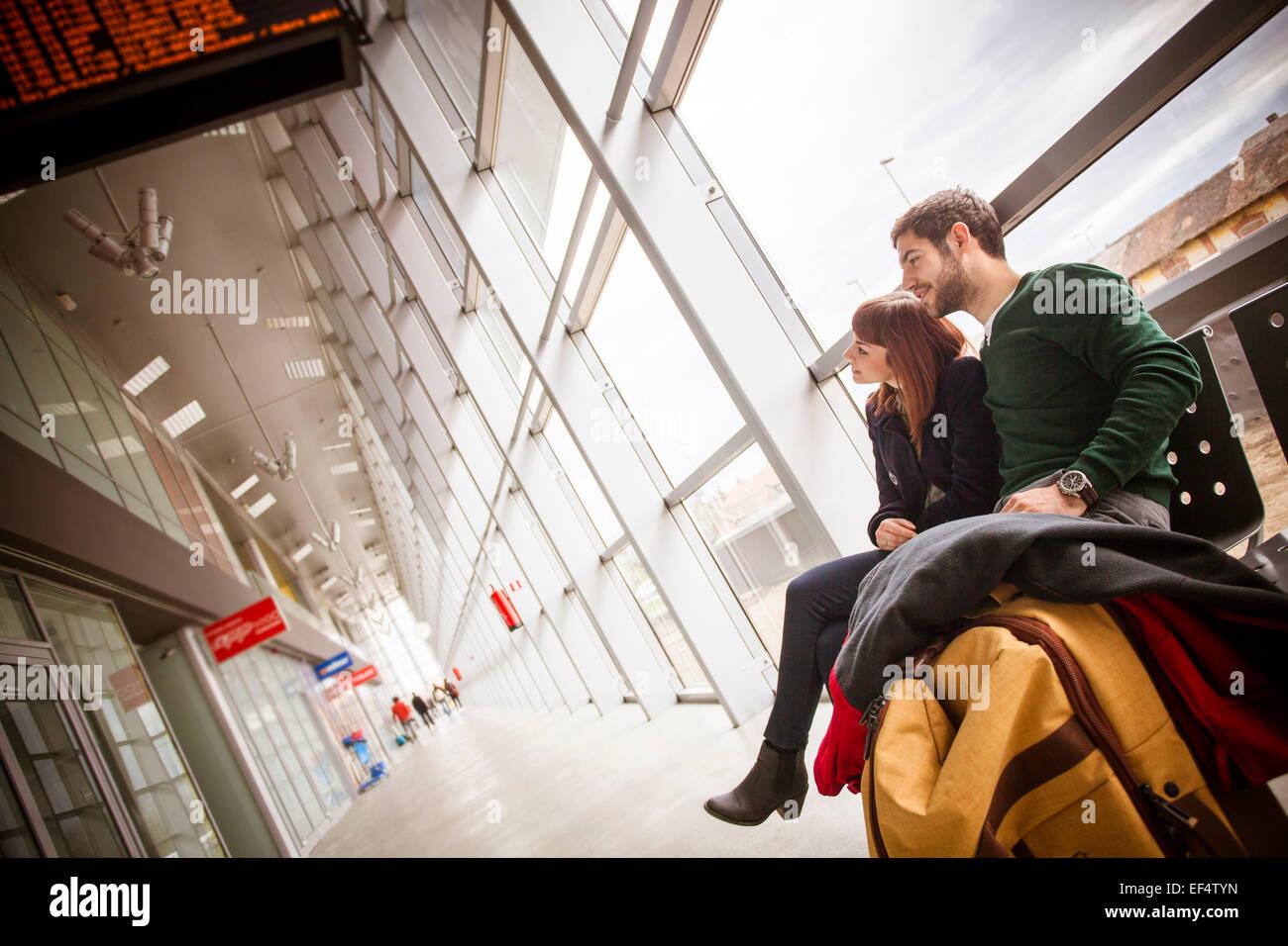 Jeune couple en attente dans bâtiment de l'aéroport Photo Stock