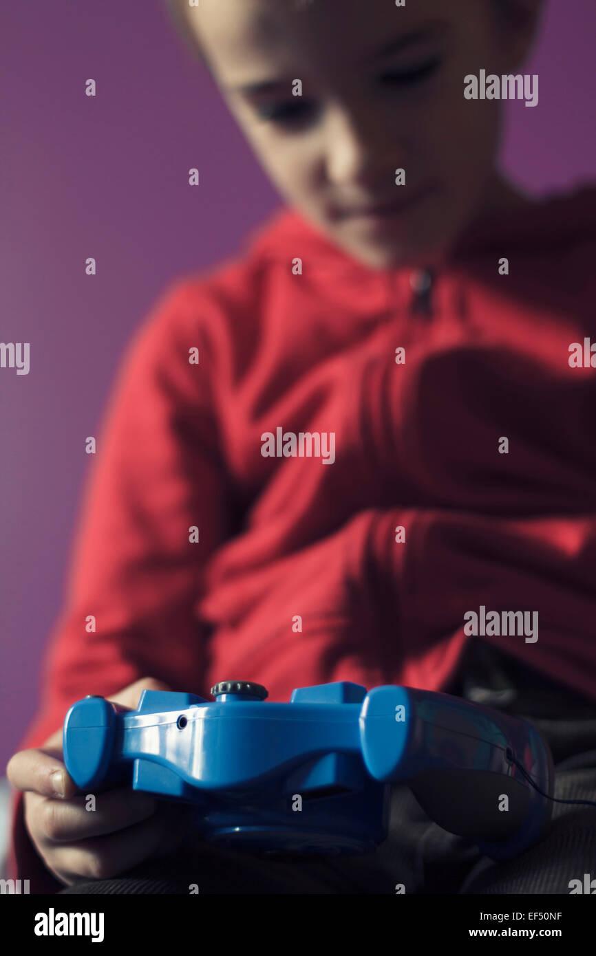 Jeune garçon à l'intérieur de la lecture d'un jeu vidéo. Photo Stock