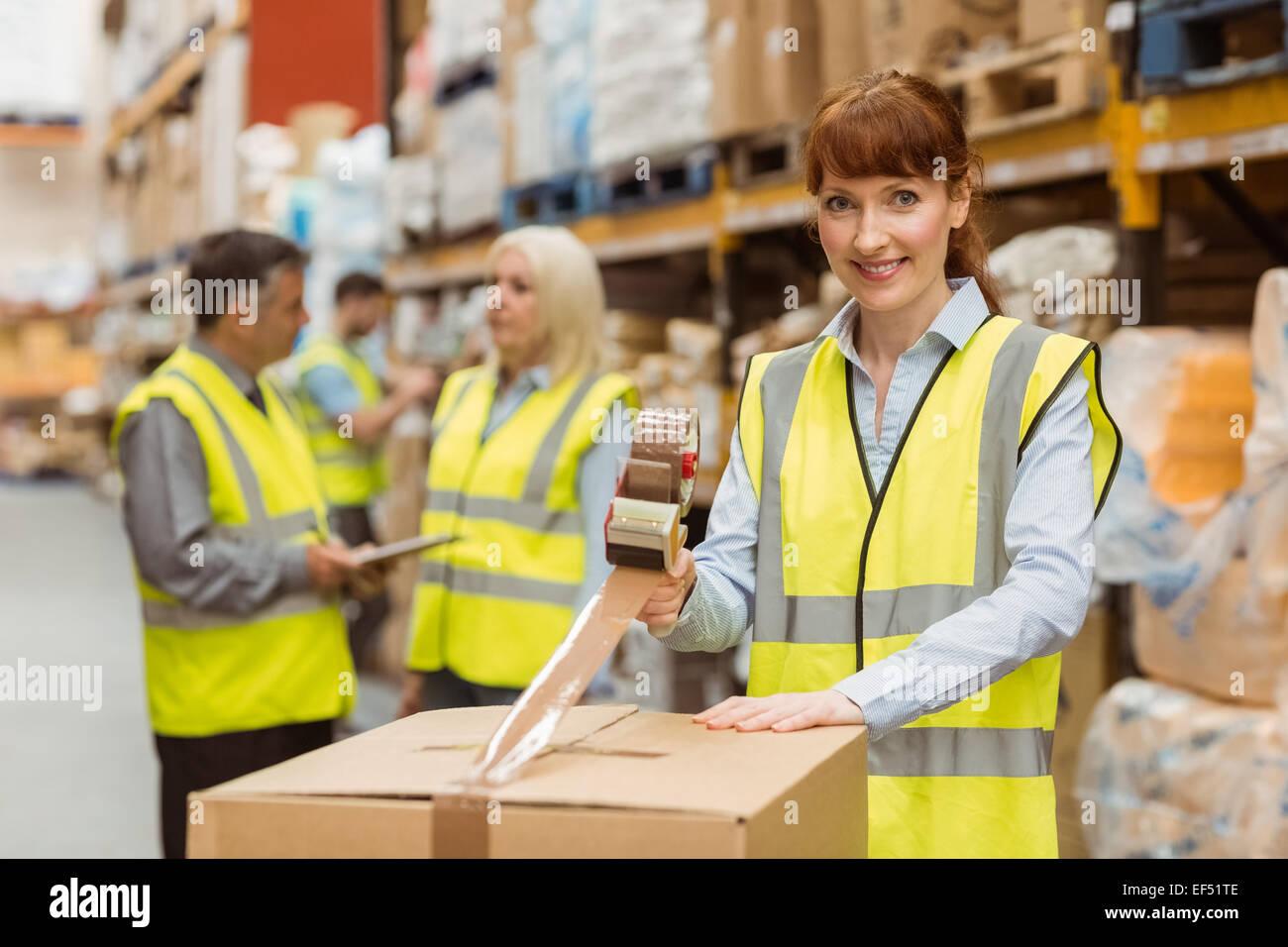 Les employés de l'entrepôt souriant la préparation d'une expédition Photo Stock