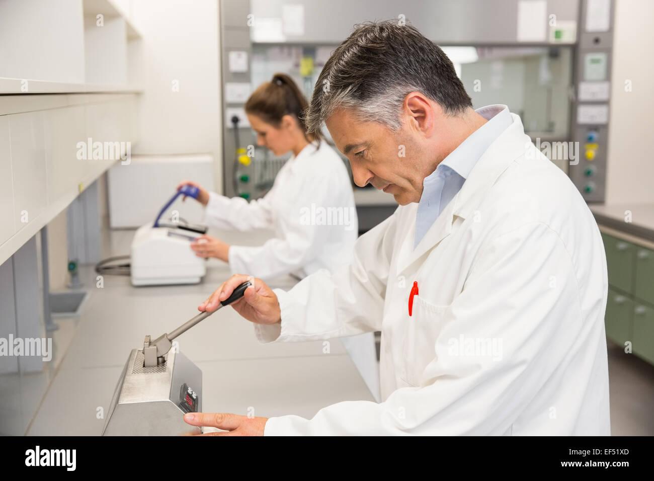Pharmacien à l'aide de appuyez sur pour faire des comprimés Photo Stock