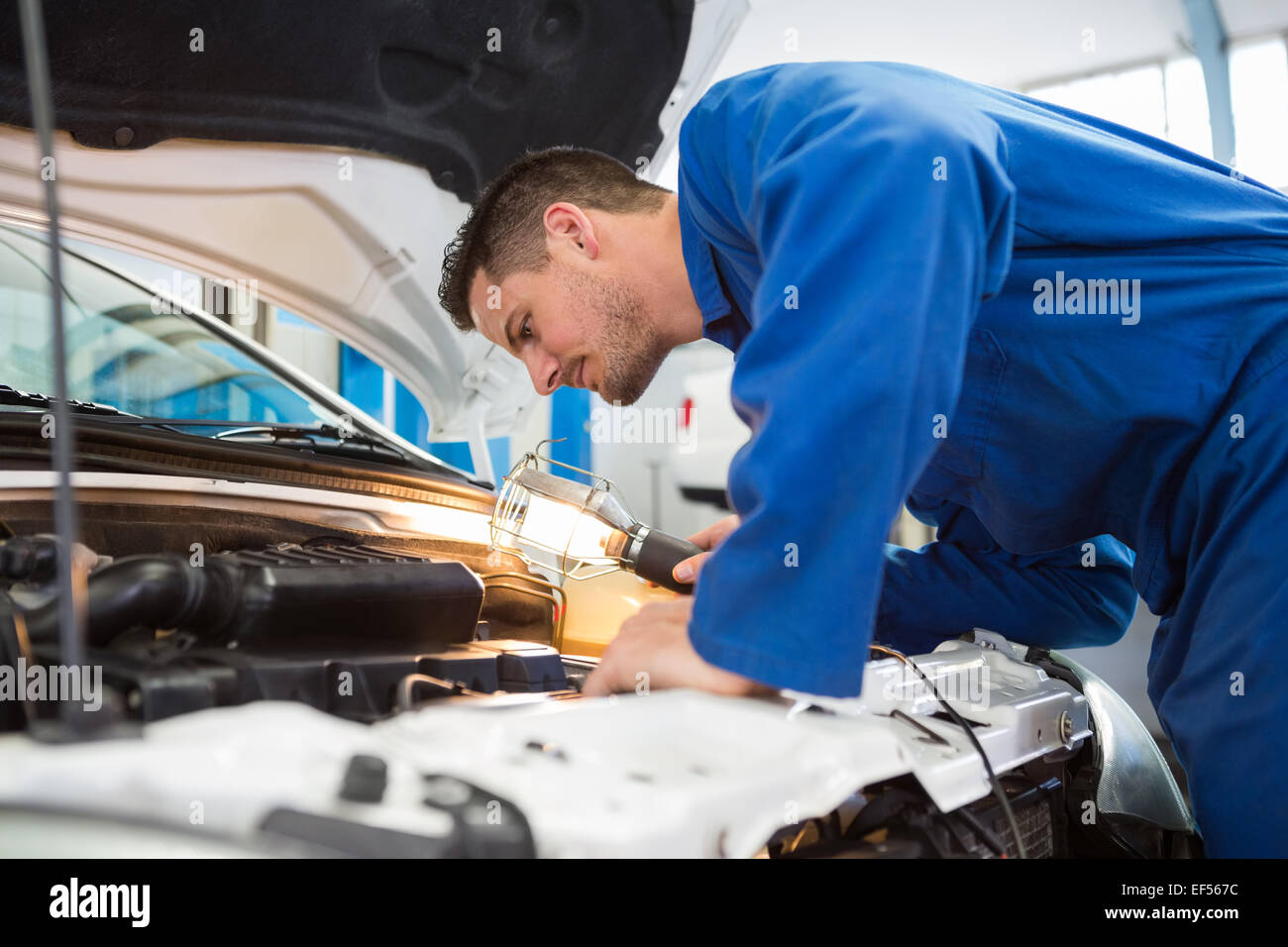 Sous le capot de l'examen de mécanicien de voiture avec torch Photo Stock