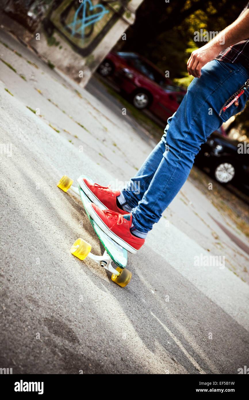 Personne méconnaissable avec la planche à roulettes chaussures de sport rouge Photo Stock