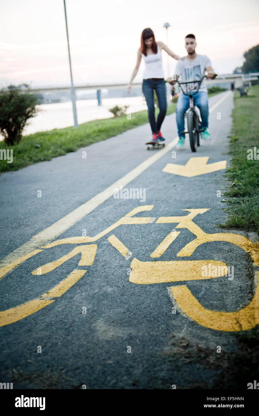 Jeune couple avec Skateboard and BMX bicycle outdoors Banque D'Images