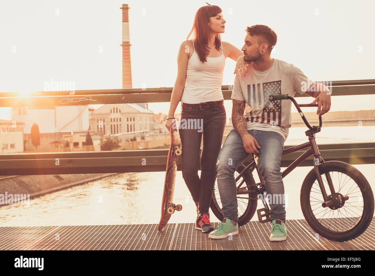 Jeune couple avec Skateboard and BMX location reposant sur bridge Banque D'Images