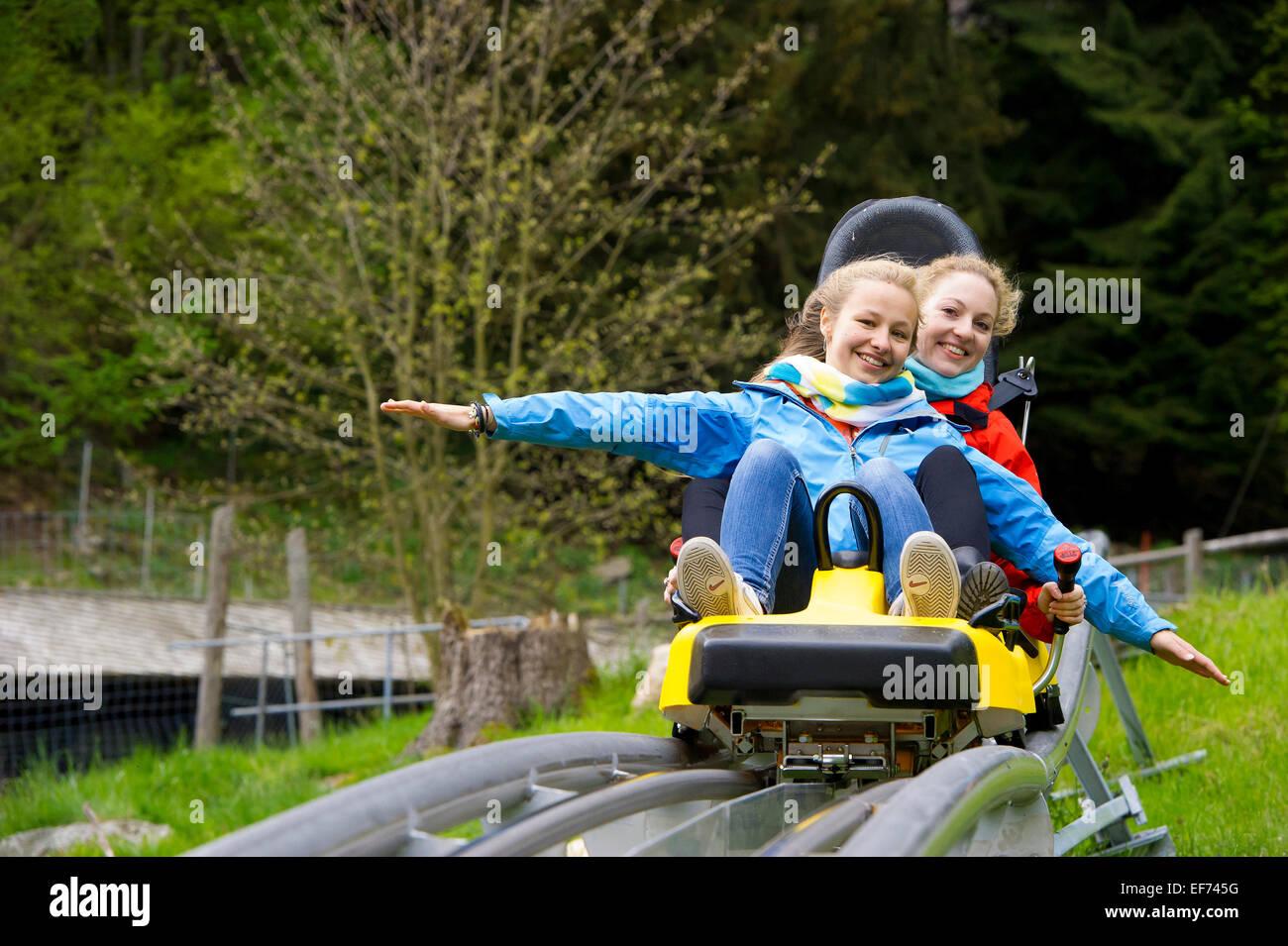 Les jeunes femmes sur une piste de luge d'été, dans le Steinwasenpark Oberried, Forêt-Noire, Photo Stock