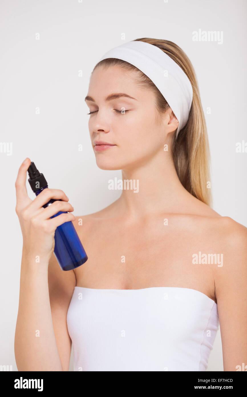 Belle femme pulvériser de l'eau sur son visage Banque D'Images